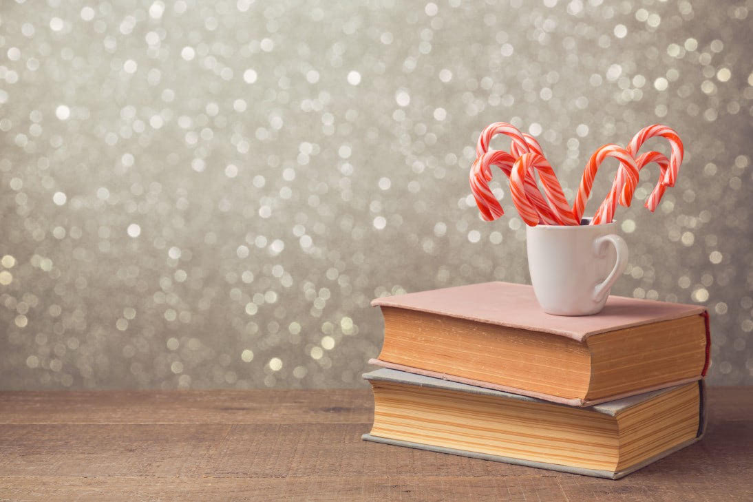 Christmas celebration with candy cane and cup on books over bokeh background